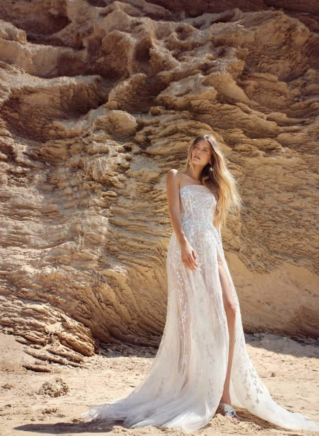 Model is on the beach and wearing a thigh-high split in the voluminous silver and sequinned embroidered tulle dress