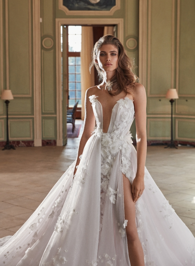 Model is standing in a manor house and is wearing a wedding dress with 3D petals