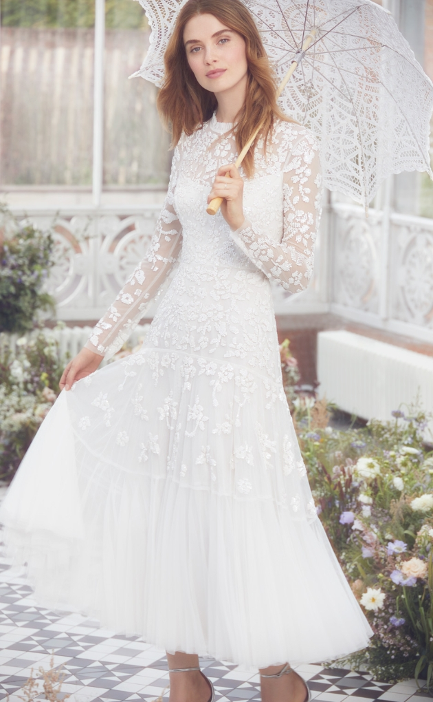 Model is in a summer house wearing a ivory lace gown decorated with sequins and petal embellishments