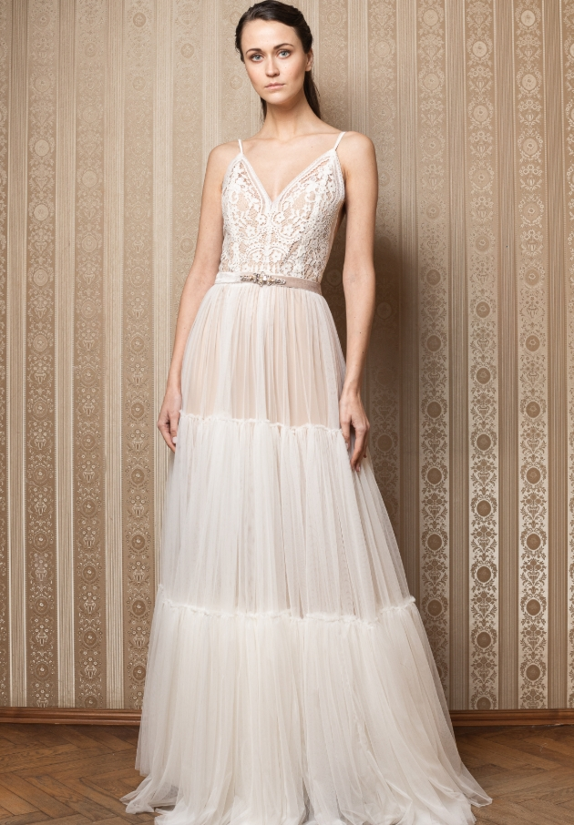 Model wears tiered tulle dress with peach underlay