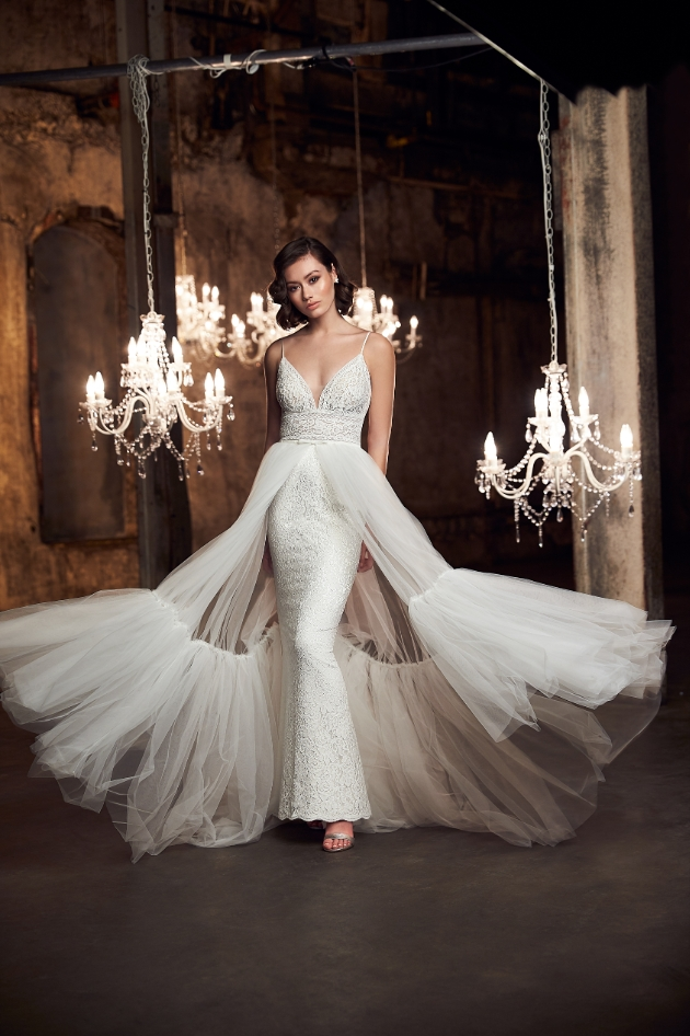 Model indoors with hanging chandeliers wears dress with large netted skirt overlay