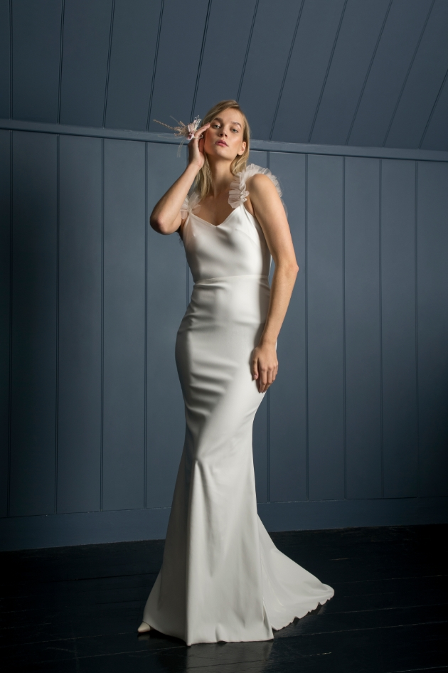 Model in front of wooden blue background wears slimline wedding dress with frill straps