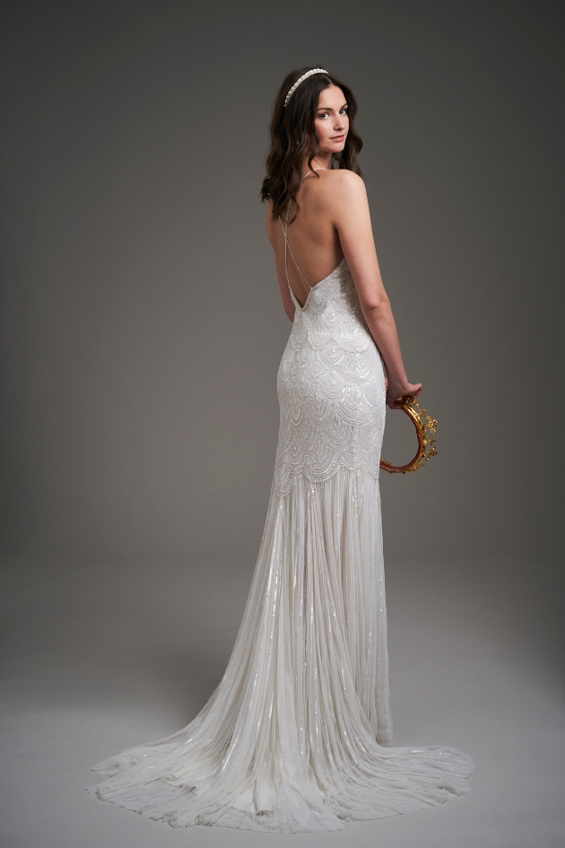 back shot of model wearing a wedding dress and holding a crown