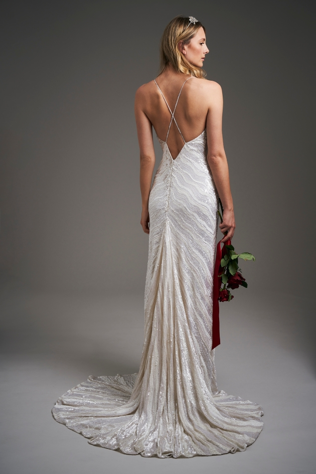 back shot of model wearing a wedding dress holding flowers