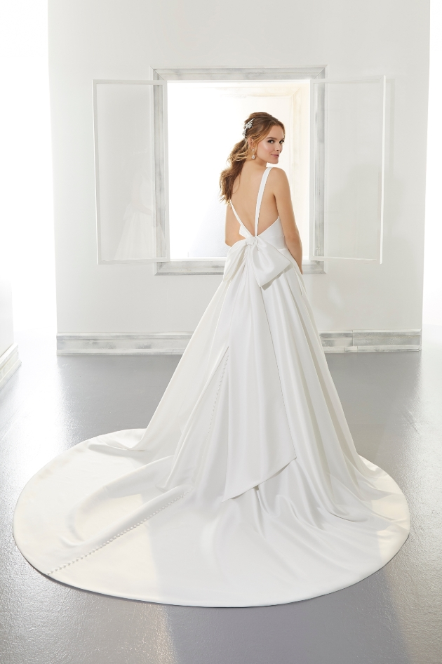 Plunge back strap wedding dress worn by model and features bow