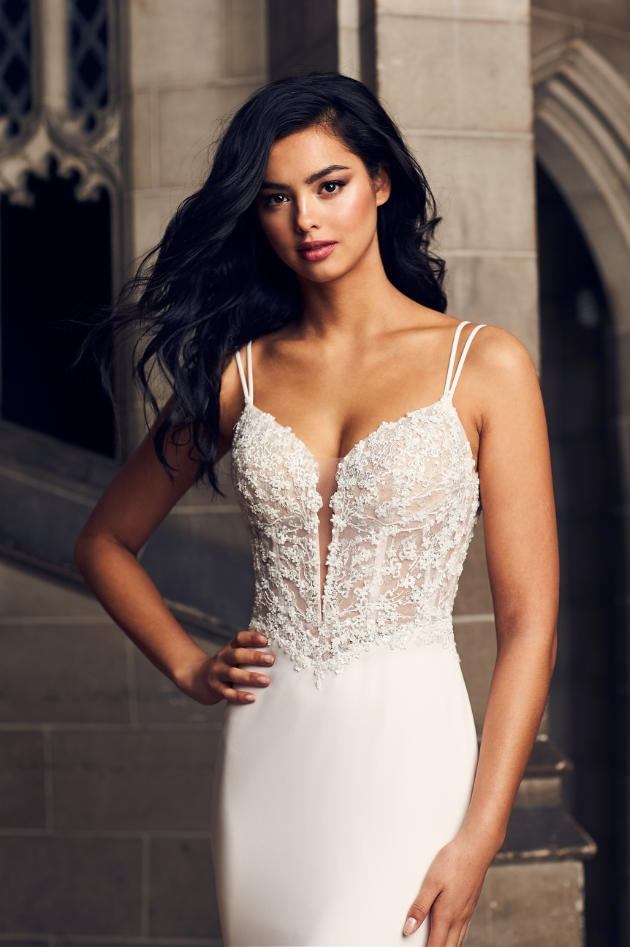 Model is wearing a wedding dress with embellished corset