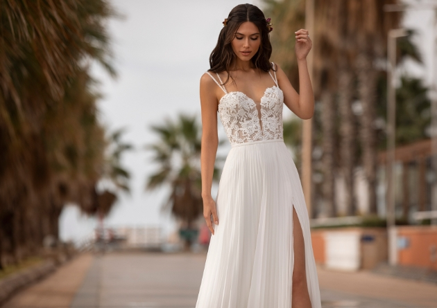 Model in the street on a hot day wearing thigh high split wedding dress