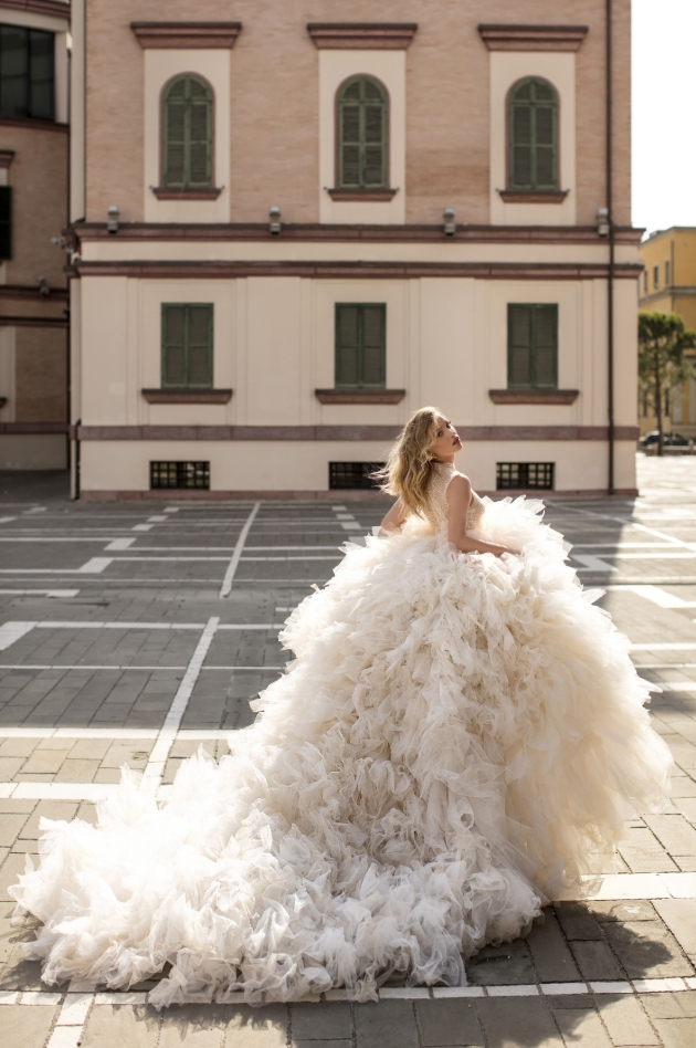 Bride running through the street in a large flamboyant dress