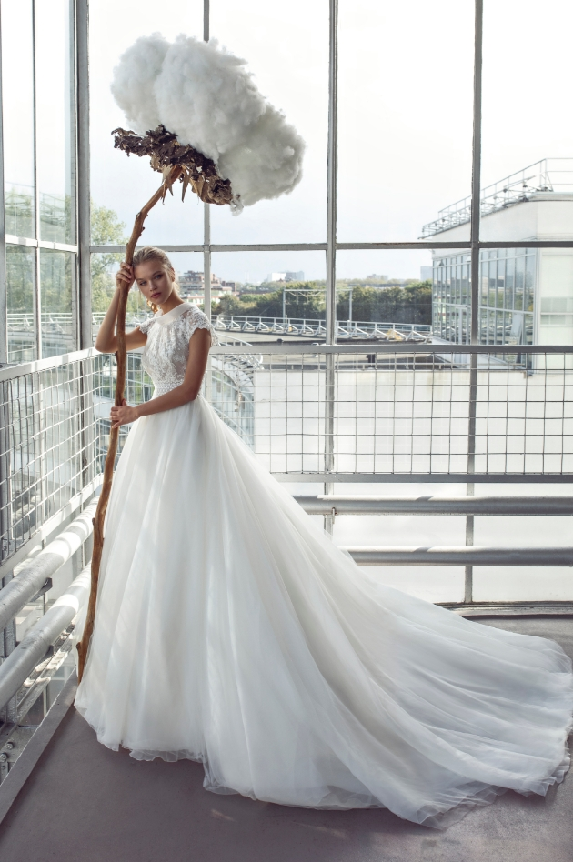 Bride standing inside a glass building holding huge flower as a prop while wearing a wedding dress