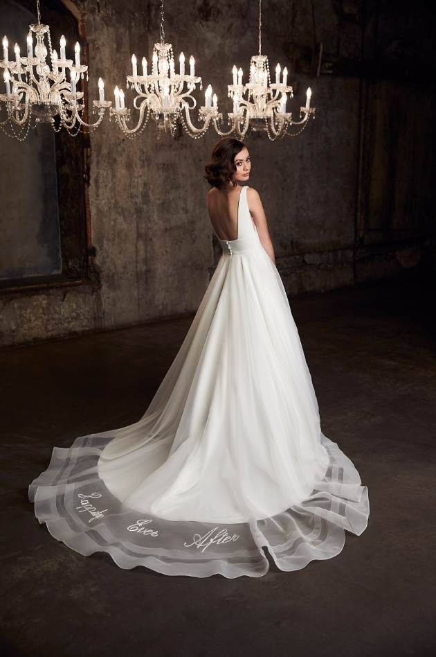 Bride in a room with chandeliers with back of wedding dress on show train laid on floor to reveal 'happily ever after' etched in
