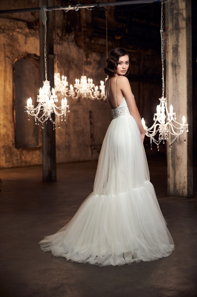 Bride in room with chandeliers, ornate looking, two-tiered dress displayed on model