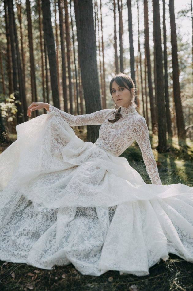 Model in the woods wearing a large billowing wedding dress