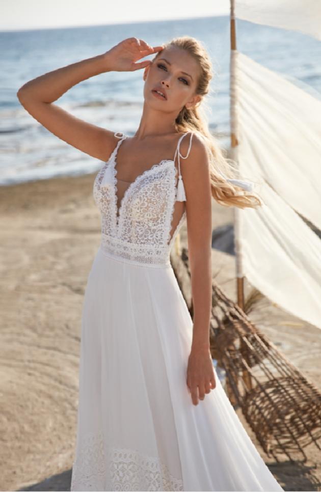 Model is on the beach wearing a wedding dress