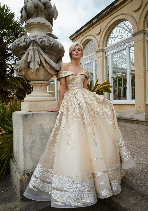 Model on a garden terraced in a gold and silver dress