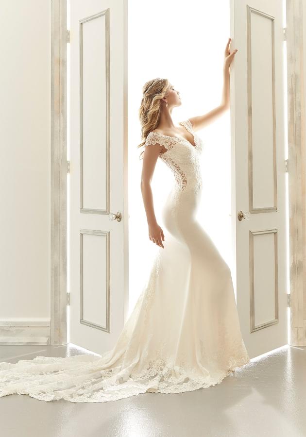 Model posing in a door way in a slim fit wedding dress