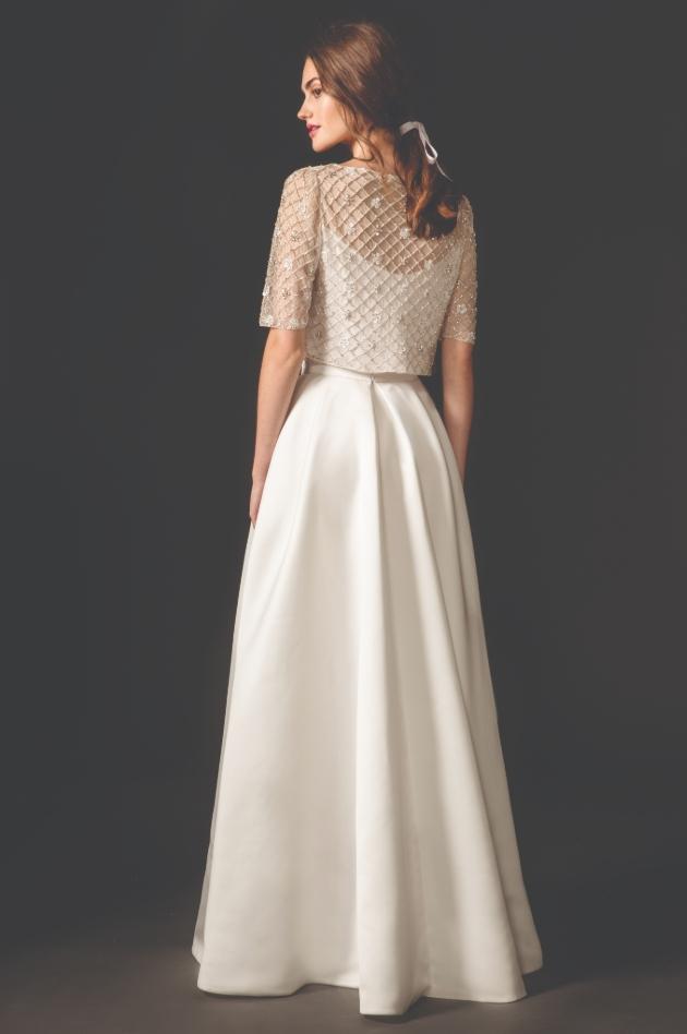Model is wearing wedding dress with jacket-style overlay
