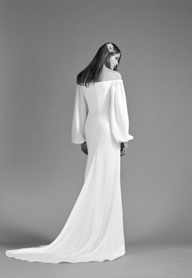 Black and white image of a model wearing a wedding dress with long cuffed sleeves and a headpiece