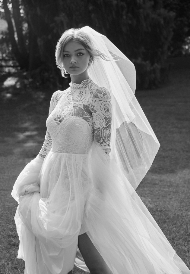Model wearing a veil, wedding dress with see-through detail and split skirt