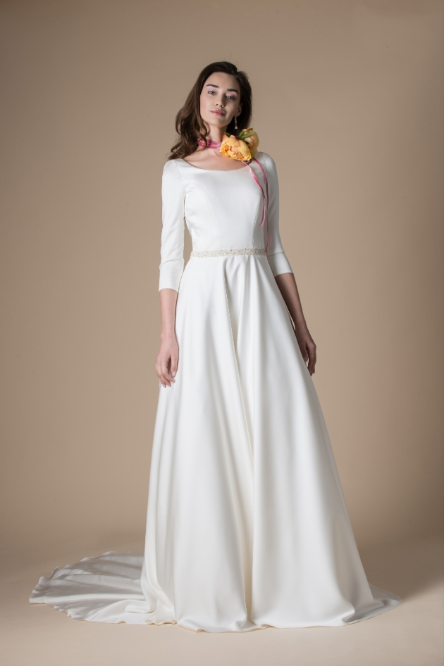 Model wears long white wedding dress and corsage necklace