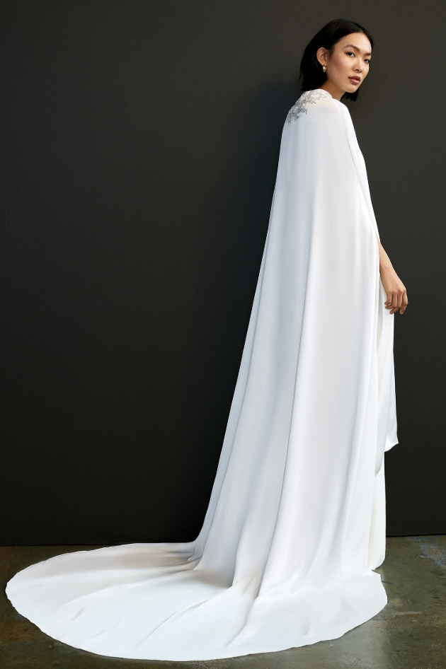 Model is wearing a floor-length white cape