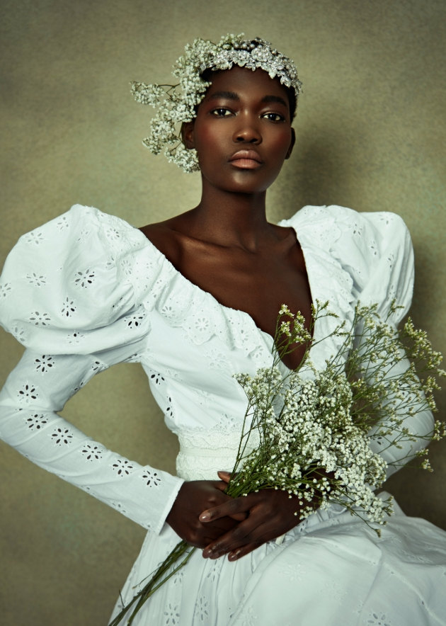 Model wears white cotton dress with puff sleeves and flower crown