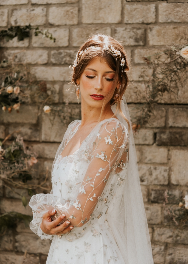Model wears dress with see-through sleeves with flower detail