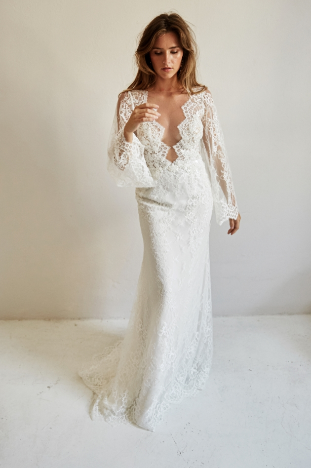 Model wears long gown with cut away neckline and long sleeves