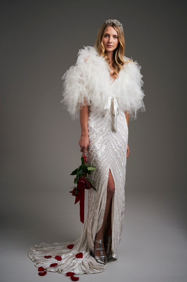 Model wears Art Deco style dress with tulle jacket and holding flowers