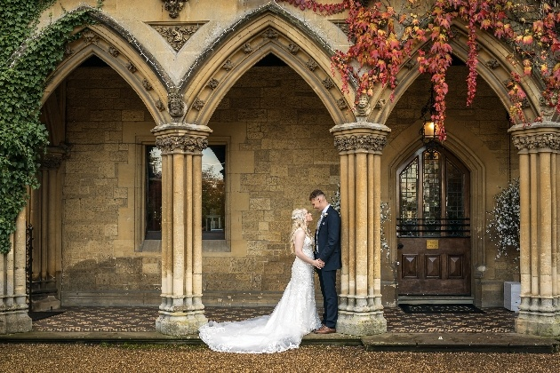 Couple pose under arch