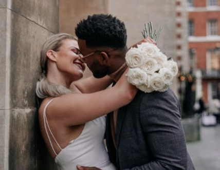 couple kissing up the side of a building in wedding outfits bride holding bouquet